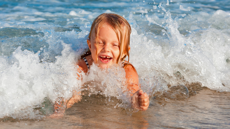 baby playing in ocean