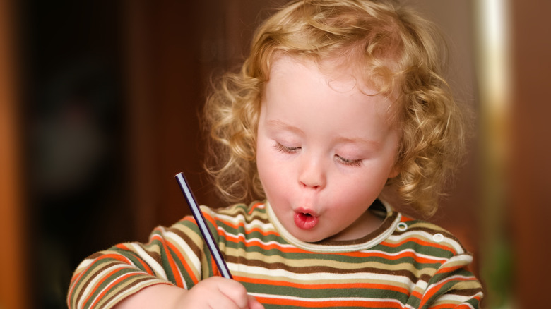 cute little girl excitedly writing