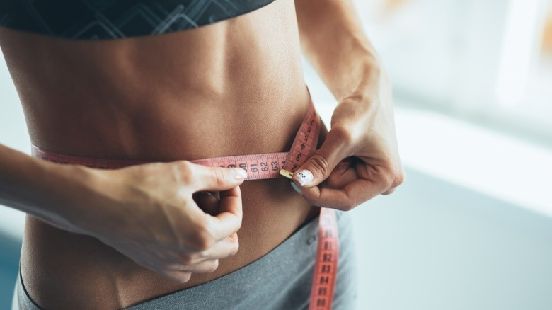 woman with visible abs using tape measure healthy unhealthy