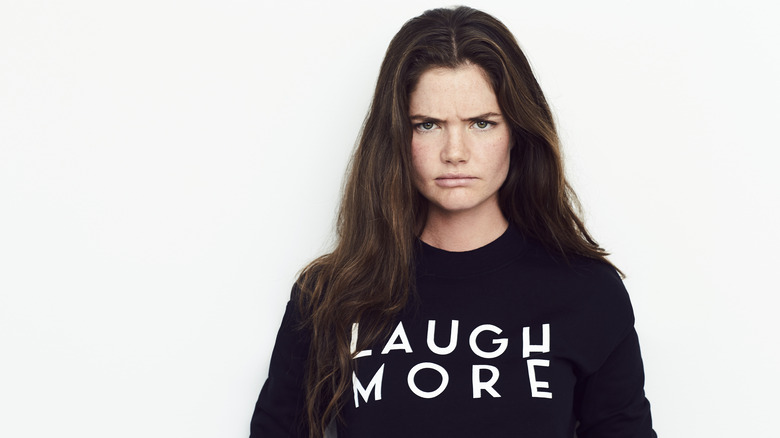 frowning woman wearing shirt with slogan laugh more