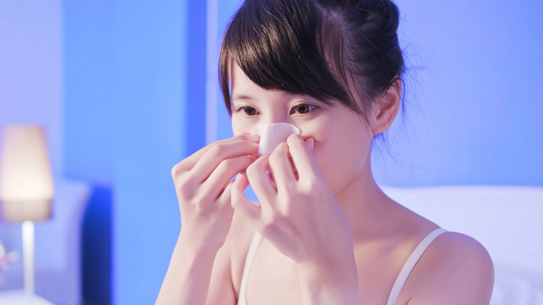 A woman prepares to take the pore strip off her nose to see if it works