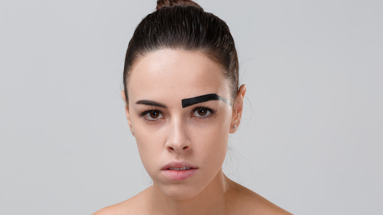 woman with one painted eyebrow