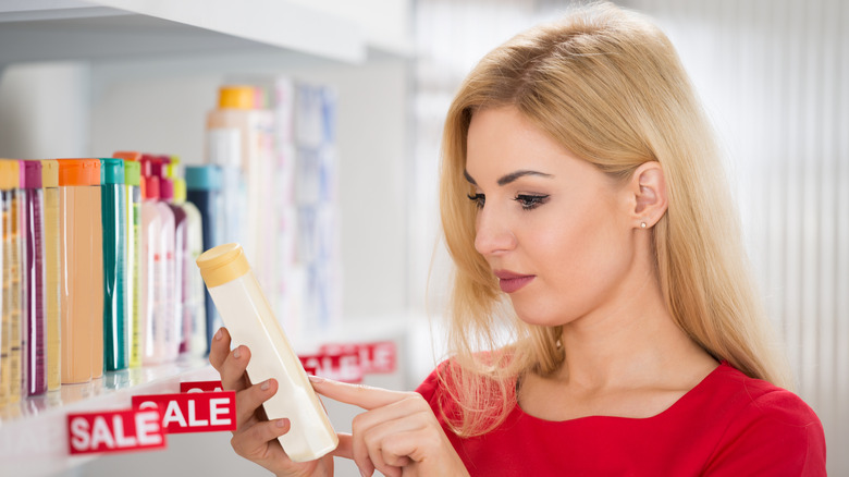 woman checking shampoo ingredients