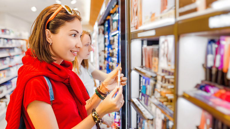 Woman shopping for Maybelline cosmetics