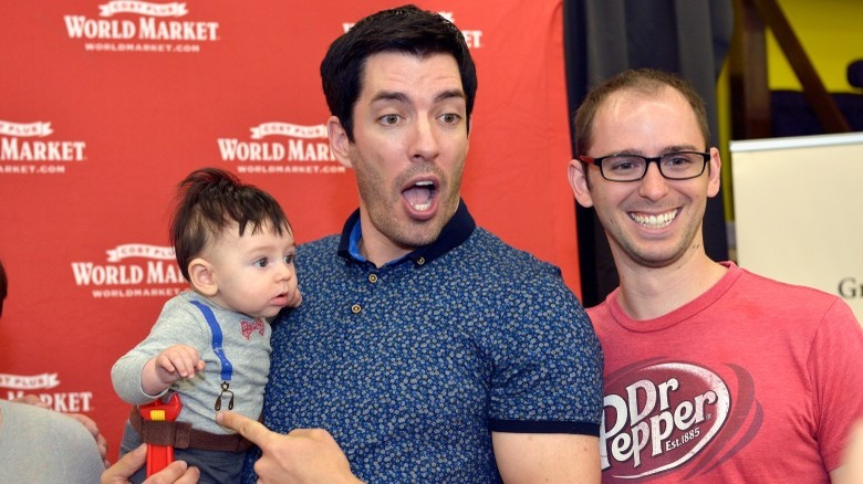 Property Brothers star Drew Scott holding a baby