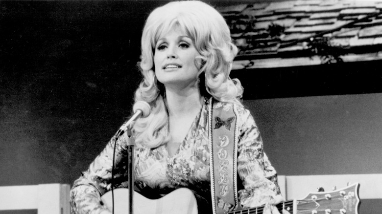 Dolly Parton playing guitar on stage in the '70s or '80s