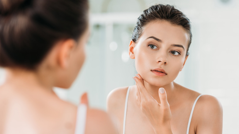 young woman looking at face in mirror