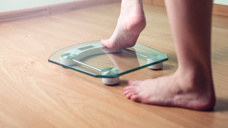 A woman's feet stepping onto a scale
