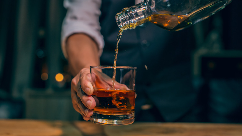 man pouring whiskey into a glass