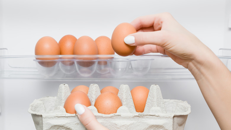 woman selecting eggs from refrigerator