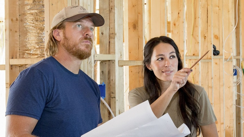 Chip and Joanna Gaines on Fixer Upper in front of beams