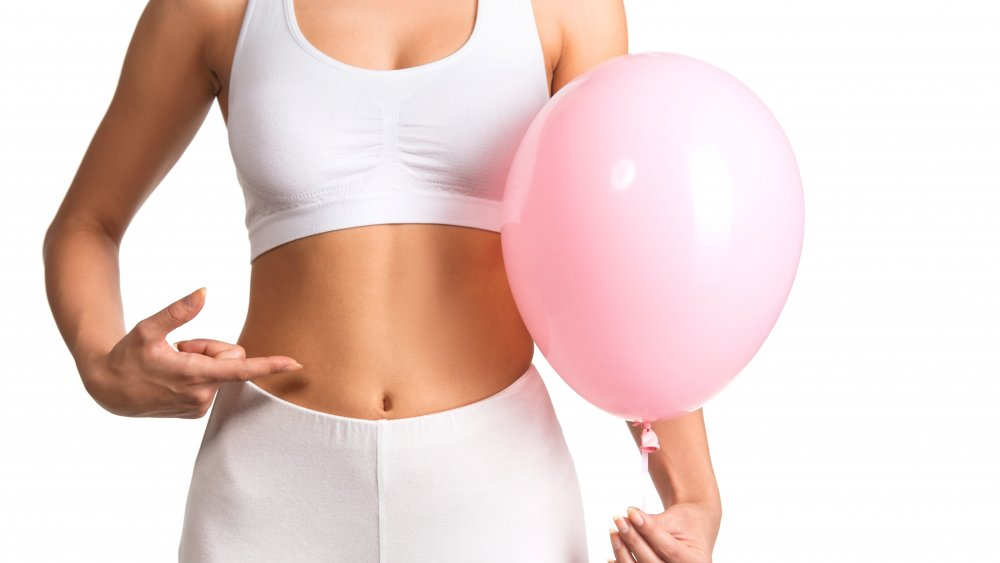 Woman pointing to stomach, holding pink balloon