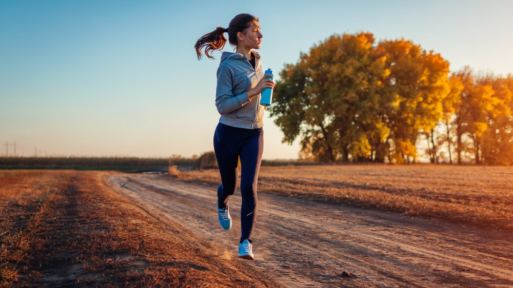 A woman jogging on a country road