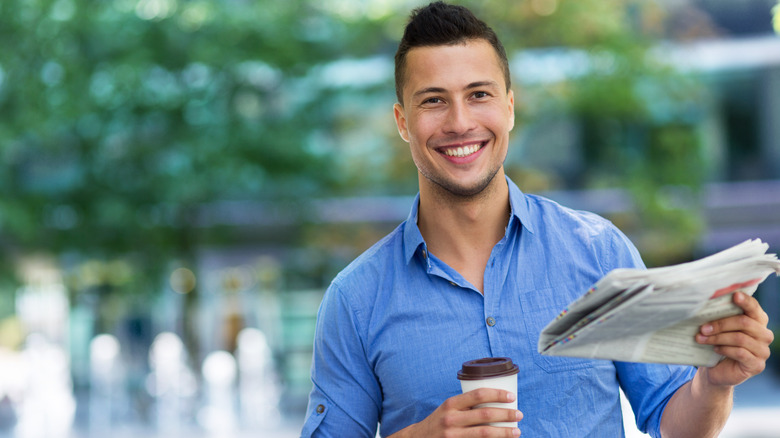 man smiling while holding a cup of coffee and newspaper