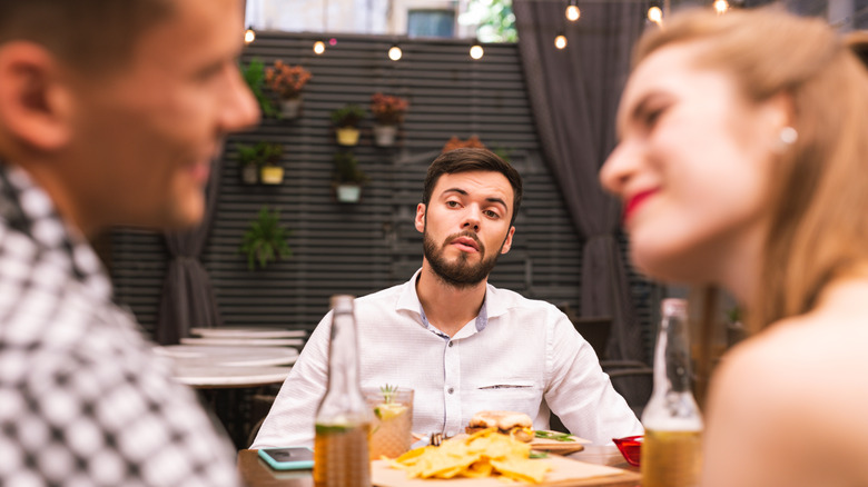 man observing couple smiling at each other